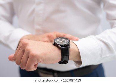Close-up of businessman checking time with wristwatch. Caucasian executive waiting for client being late. Time and punctuality concept
