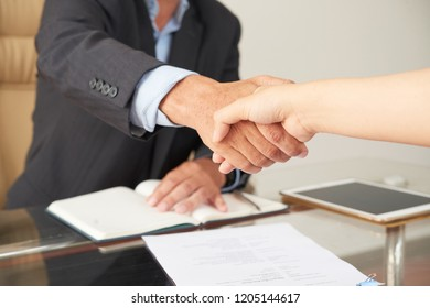 Close-up of businessman concluding a deal with businesswoman after signed the contract