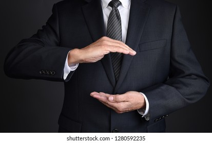 Closeup of a businessman with cupped hands as if holding something. Man is unrecognizable.