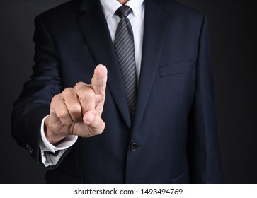 Closeup of a businessman in a dark gray suit and tie pressing the screen with his index finger.