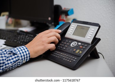 Closeup of businessman dialing making office phonecall, light table background. Corporate male holding telephone handle digital electronic pc connection checking daily data news, online chat talk job