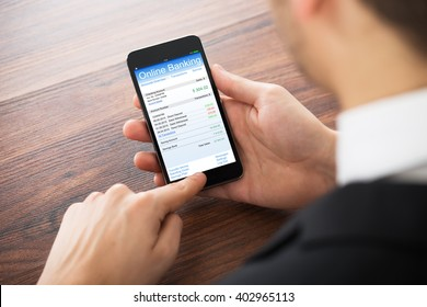 Close-up Of Businessman Doing Online Banking On Mobilephone At Office Desk