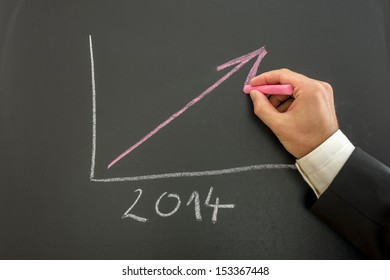 Closeup of businessman drawing growing financial business graph for year 2014.