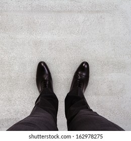 Close-up of businessman feet in black boots on the floor