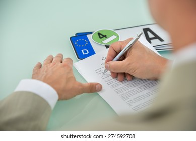 Close-up Of A Businessman Filling Car Sale Contract Form With Vehicle Registration Plate On Desk. Contract Paper Contains Placeholder Text