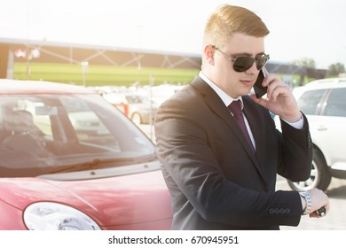 Close-up of a businessman in front of his office building. Young ambitious businessman talking on his phone while standing in a car parking lot. Looking at his watch while on the phone.
