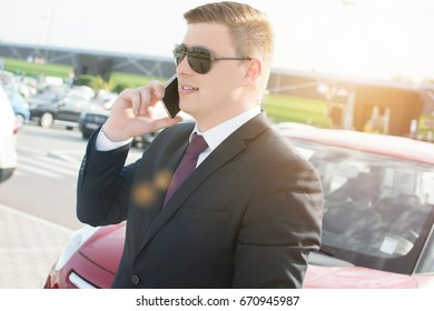 Close-up of a businessman in front of his office building. Young ambitious businessman talking on his phone while standing in a car parking lot. Suit and tie businessman having a conversation.