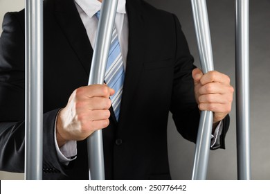 Close-up Of Businessman Hand Bending Bars Of Jail
