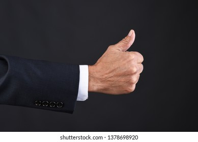Closeup of a businessman hand giving the thumbs up signal, expressing approval.
