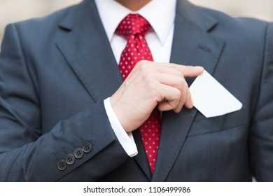 Closeup of Businessman hand holding a business card over suit pocket Isolated on white. Businessman in suit and red tie drawing white business card into pocket. Close up of man hand with card
