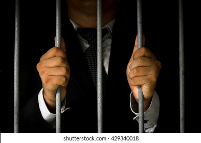Close-up Of Businessman Hand Holding Metal Bars In Jail with dar