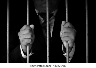 Close-up Of Businessman Hand Holding Metal Bars In Jail in a dark environment