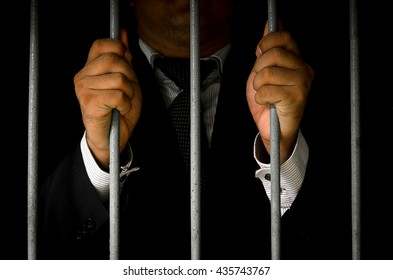 Close-up Of Businessman Hand Holding Metal Bars In Jail with dark environments.