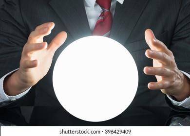 Close-up Of Businessman Hand On Crystal Ball On Desk