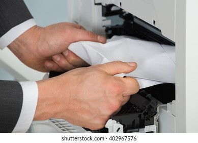 Close-up Of Businessman Hand Removing Paper Stuck In Printer At Office
