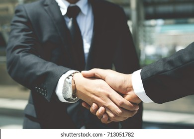Closeup of a businessman hand shake between two colleagues OK, succeed in business.