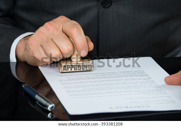 Close-up Of Businessman Hand Stamping On Approved Contract Form On Desk