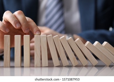 Close-up of businessman hand stopping process of light wooden blocks falling. Prevention and development to stability. Risk in business and economy concept