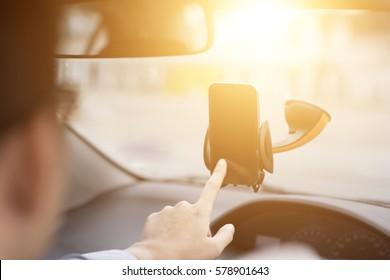 Close-up of Businessman Hand Using GPS Navigation Inside Car.