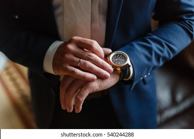 Closeup with businessman hands closing elegant blue suit jacket and wearing banker expensive wrist watch