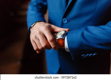Closeup with businessman hands closing elegant blue suit jacket and wearing banker expensive wrist watch. The clock on the hand