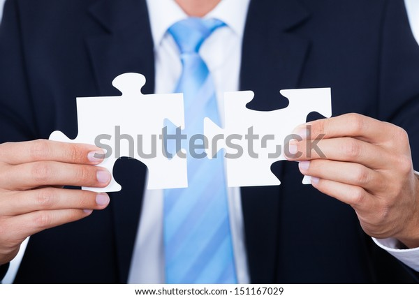 Close-up Of Businessman Hands Connecting Jigsaw Puzzle
