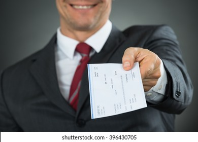 Close-up Of Businessman Hands Giving Cheque In Office
