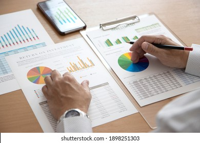 Closeup of businessman hands holding a pencil while reviewing financial statements for business performance or return on investment, ROI analysis.