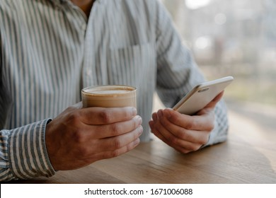 Closeup of businessman hands holding smartphone, drinking coffee, reading e-mail. Freelancer searching on website, online shopping, using modern application