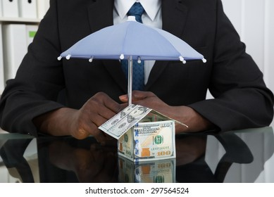 Close-up Of Businessman Hands Protecting House Of Banknote With Umbrella At Desk