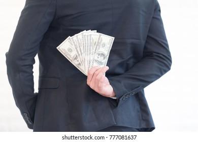 Closeup of businessman hiding money on back.
