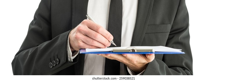 Closeup of businessman holding blue clipboard folder writing notes and observations with ink pen.