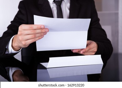 Close-up Of Businessman Holding Document At Desk