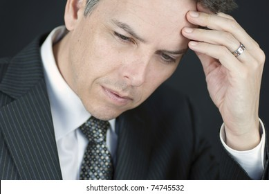 Close-up of a businessman holding his head in his hand.