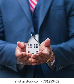 Close-up of businessman holding house model in hands. Mortgage, loan, rent, real estate purchase