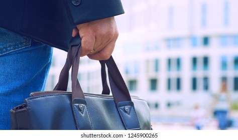 Closeup of a businessman holding a leather bag handle.