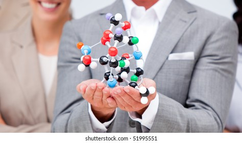 Close-up of a businessman holding a molecule with his team in the background