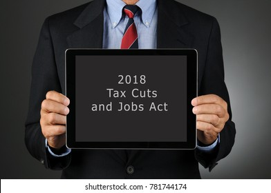 Closeup of a businessman holding Tablet Computer with 2018 Tax Cuts and Jobs Act on the screen. Horizontal format over a light to dark gray background.