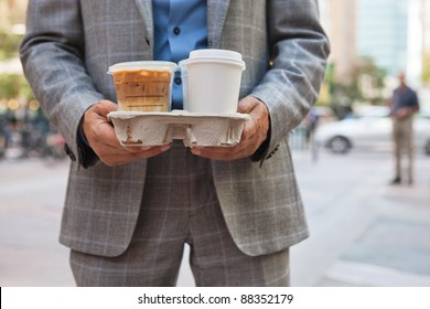 Close-up of businessman holding takeaway coffee cups