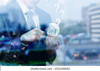 A closeup of a businessman with house model and magnifier in his hands with question marks above and insurance system in front at the blurred city background. The concept of comprehensive insurance.