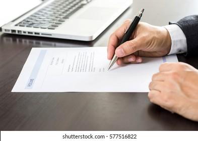 Close-up Businessman or job seeker signing on resume form.