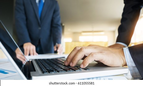 Closeup of businessman is keyboarding on portable net-book, while is sitting in modern office interior. Closely of a successful male entrepreneur is using laptop computer during work day in company.