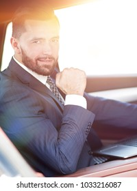 Close-up of a businessman with a laptop sitting in the car