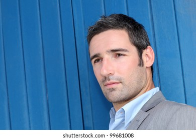 Closeup of businessman leaning on blue background