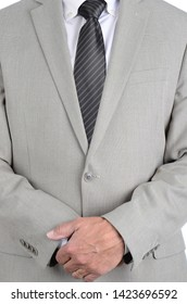 Closeup businessman in a light gray suit and gray striped tie with hands clasped in front, torso only man is unrecognizable.