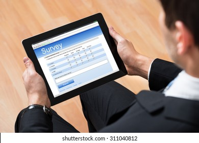 Close-up Of Businessman Looking At Blank Online Survey Form On Digital Tablet