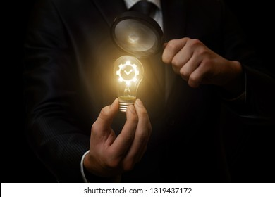 A closeup of a businessman looking at the lightbulb with a gear mechanism containing the quality sign inside through the magnifier. The concept of successful innovative idea.