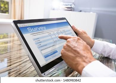 Close-up Of Businessman Looking At Online Survey Form On Digital Tablet