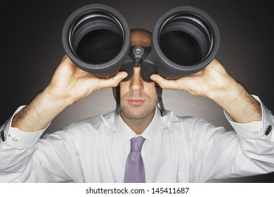Closeup of a businessman looking through large binoculars against gray background