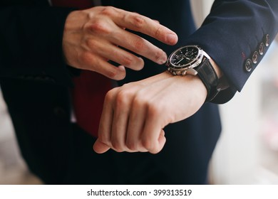 closeup businessman looks at his watch day light